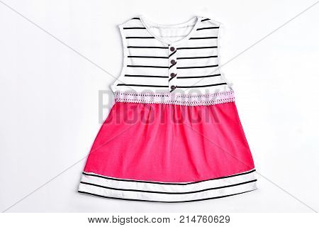 Top quality fashion baby dress. Beautiful striped and pink sleeveless dress with embroidered belt for baby-girl, white background. Elegant sundress for baby-girl.