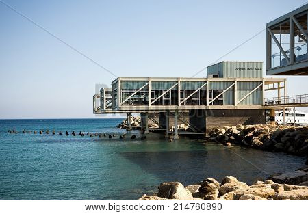 Limassol, Cyprus, July 2017: A steak house restaurant on posts hanging over water in Limassol Marina harbor Cyprus