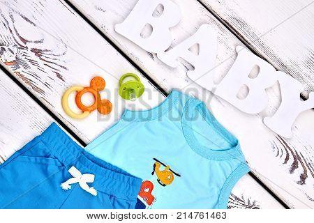 Toddler boy modern summer apparel. Little boy high quality textile shorts, sleeveless cartoon t-shirt, accessories. Baby boy summer outfit background.