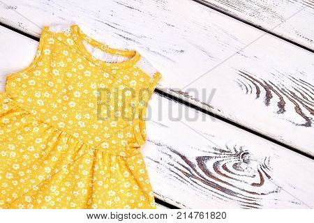 Baby-girl cute sleeveless top. Infant girl summer casual cotton dress, vintage wooden background.