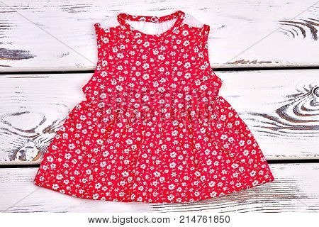 Toddler girl vintage print top. Baby-girl cute red sundress with a pattern of small white flowers, top view.