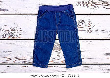 Infant kids denim trousers on sale. Baby boy or girl jeans on old wooden background. Infants brand garment.