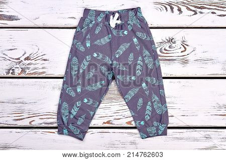 Fashion design trousers for kids. Dark blue printed pants for toddler kids on wooden background. Baby patterned harems.