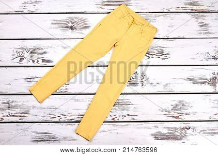 Girls yellow cotton trousers, top view. Teen lady high quality summer pants on white wooden bacground. Young women denim apparel.