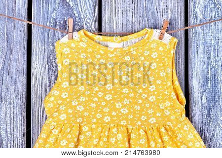 Baby girl sleeveless yellow top. Infant baby-girl cotton dress drying on rope on old wooden background. Kids clothing in laundry.