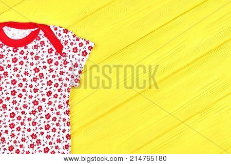Baby girl white and red t-shirt. Infant girl new patterned summer bodysuit on yellow wooden background, copy space. Hot sale of infants summer apparel.