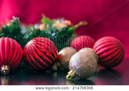 Red and gold Christmas ball ornaments are placed on a black reflective table top surface. The ball ornaments are different sizes and are shiny and matte colored. The ornaments reflect off the table. Behind the ornaments is a green Christmas wreath and a r