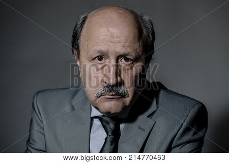 portrait of sad and depressed senior mature business man on his 60s suffering depression looking lost and thoughtful wearing necktie isolated on dark background in sadness face expression