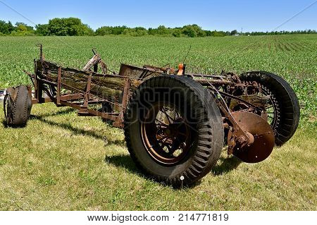 Remains of a very old manure spreader near a cornfield  which has decomposed to the metal frame