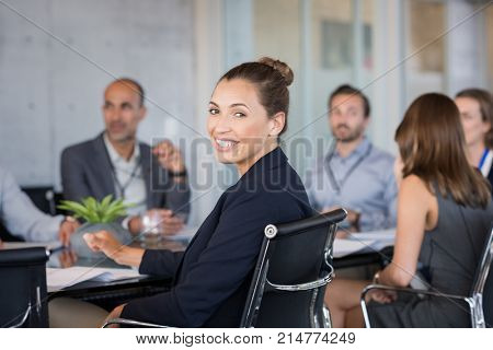 Young beautiful businesswoman with colleagues sitting in a modern board room. Proud smiling business woman sitting during a meeting and looking at camera. Happy businesswoman with executives working.