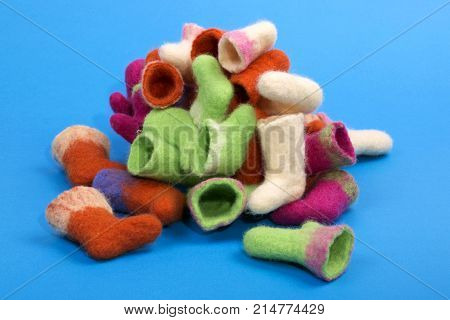Heap of souvenir boots made of felted wool on a blue background