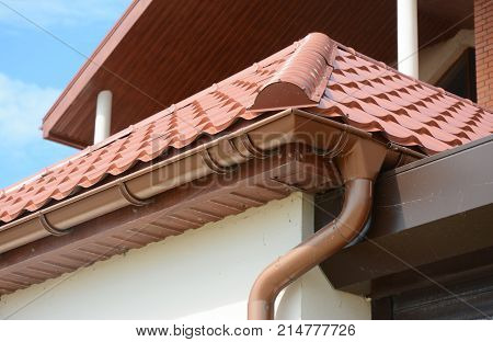 Close up on roof gutter holder and guttering downspout pipe with clay tiles roof. Installing rain gutter.