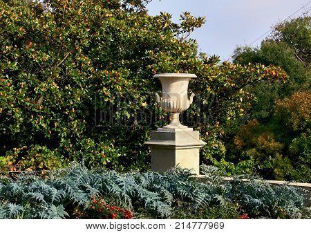 Decorative marble white vase on a stone pedestal among plants