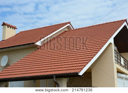 Cozy house with balcony clay tiled roof and gable and valley type of roof construction. Building attic house construction with different types of roof designs