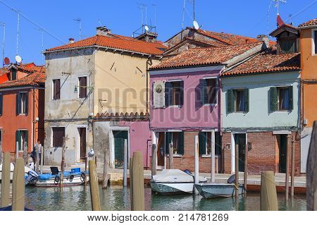 VENICE-ITALY SEPTEMBER 21 2017 : Murano island view on the canal in the middle of the city colorful houses. Murano is a series of islands connected by bridges in the Venetian Lagoon. It is famous for its glass making