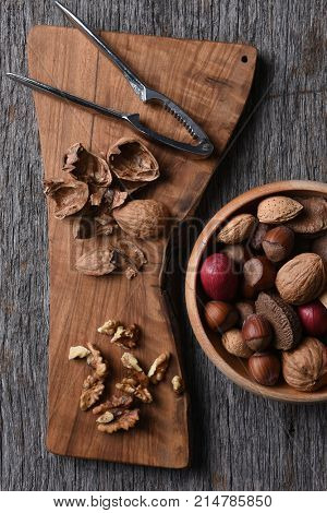 Cracked walnuts and nutcracker on a cutting board with a bowl of mixed whole shelled nuts.