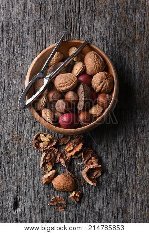 Top view of a bowl of mixed nuts with nutcracker and cracked nuts on a rustic wood table.
