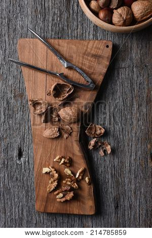 Cutting board with cracked walnuts and nutcracker with a bowl of mixed nuts int he corner.