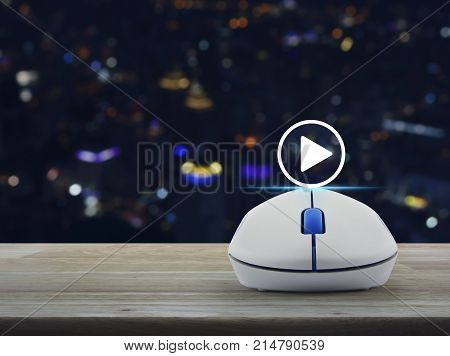 Play button with wireless computer mouse on wooden table over blur colorful night light city tower Business music online concept