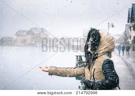 Happy woman on a snowy day - Young woman dressed for cold weather laughing and holding her hand to catch the snowflakes of the first snowfall in Hallstatt Austria.