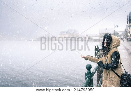 Happy woman on a snowy day - Winter weather theme image with a young woman smiling and holding hand to catch snowflakes by the Hallstatter lakeshore in Hallstatt village Austria.