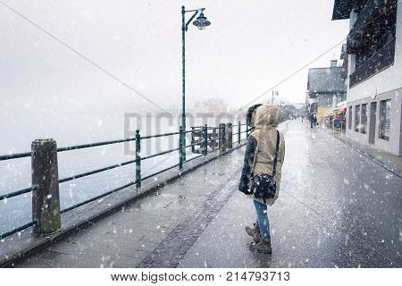 Woman walking while snowing - Winter weather theme image with a woman dressed for cold walking on the street under the snowfall near the Hallstatter lake in Hallstatt town Austria.