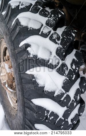 Close-up snow-covered big truck wheel with deep tread.
