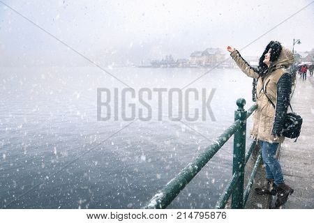 Woman reaching snowflakes on a snowy day - Happy young woman enjoying the first snowfall reaching to catch snowflakes on the Hallstatter See lakeshore in the Hallstatt town in Austria.