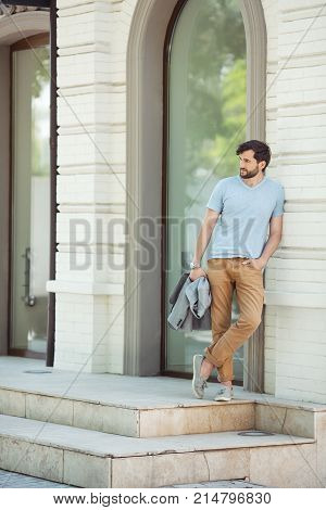 Young urban businessman professional wearing standing in full length against business building on street and looking away