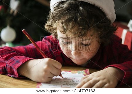 Caucasian kid writing a Christmas wishlist