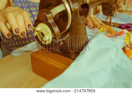 woman seamstress sitting and sews on sewing machine. Dressmaker work on the sewing machine. Tailor making a garment in her workplace. Hobby sewing as a small business concept