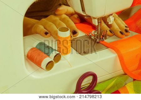 woman's hands using sewing machine with reels of colour threads. Workplace of tailor. people needlework and tailoring concept - tailor woman threading needle of sewing machine