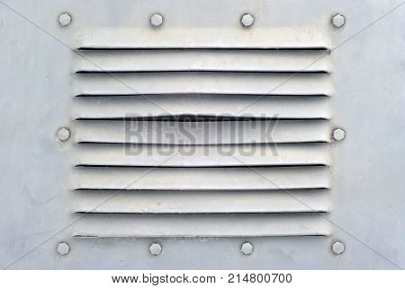 background in the military style: a section of a metal ight grey wall or shell of some armored vehicle with bolts and ventilation slits