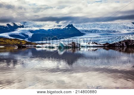 The grand spectacle - sunset over the glacier Vatnajokull, Iceland's largest glacier. Glacier provides water Ice Lagoon Jokulsarlon. The concept of extreme northern tourism