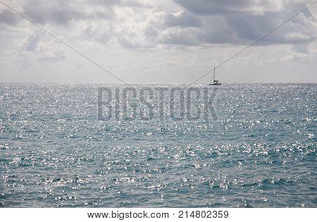 Sailing boat on a horizon on sunny shiny day