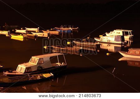 Several small boats in a marina at night