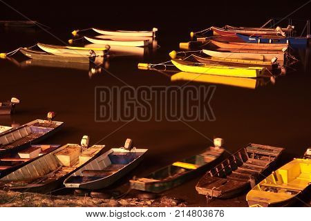 Several small fishing boats in a marina at night