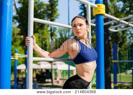 Young athletic girl in a bright blue sport bra and black leggings leaning against the horizontal bar on the sport playground. Photo of girl with a beautiful sports body