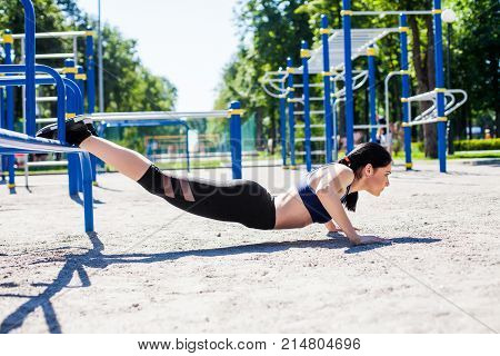 healthy sportive teen in a bright blue sport bra and black leggings doing push ups on the sport playground. Photo of an athlete girl with a beautiful sports body