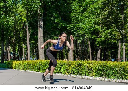 Young sportive teen in a bright blue sport bra and black leggings running in the park. Photo of an athlete girl with a beautiful sports body