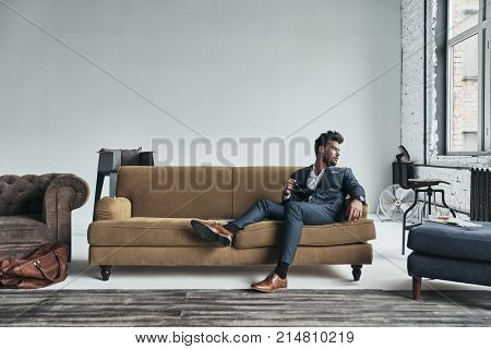 Enjoying free time. Thoughtful young man in full suit looking away while sitting on the sofa at home