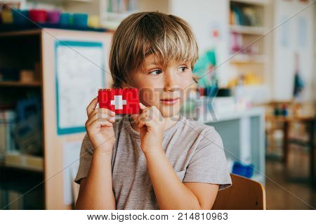 Cute little boy working in classroom holding self made swiss flag swiss primary education