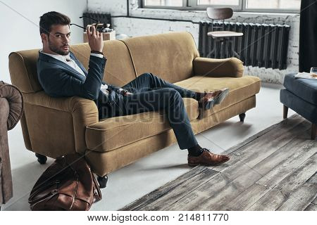 Looking into your heart. Handsome young man in full suit holding eyewear and looking at camera while sitting on the sofa