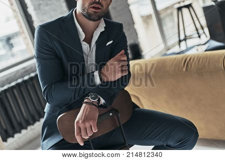 Stylish man. Close-up of young man in full suit sitting on the stool while spending time at home