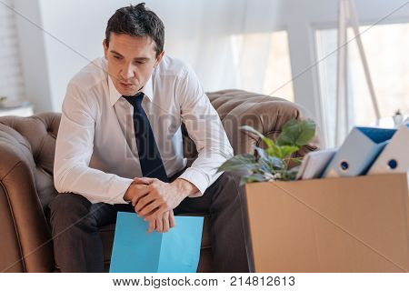 Thinking over. Clever concentrated serious man sitting in an armchair with an important document in his hand and thinking about his lost job while a big box with personal items standing by his side