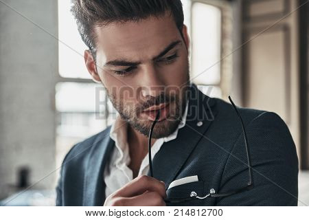 Serious look. Thoughtful young man in full suit looking down while spending time at home