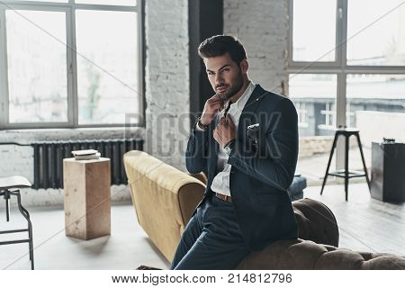 Thinking about... Handsome young man in full suit adjusting his shirt while leaning on the sofa