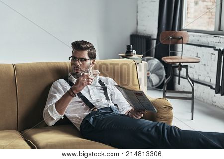 Great way to relax. Stylishly dressed young man reading a newspaper and holding a glass while sitting on sofa