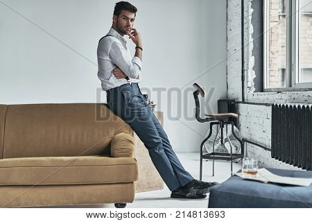 He is looking into your heart. Full length of thoughtful young man in white shirt and suspenders looking at camera and keeping hand on chin while leaning on the sofa