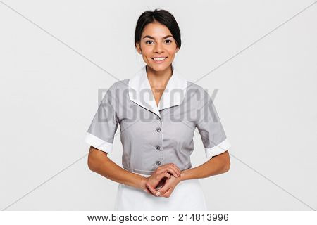 Portrait of pretty smiling maid in uniform keeping hands together and looking at camera, isolated on white background